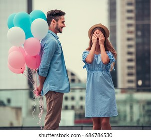 Romantic couple walking in the city. Girl is covering her eyes waiting for surprise, guy is holding balloons behind his back