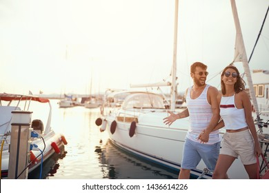 Romantic couple walking near the yachts on the dock.