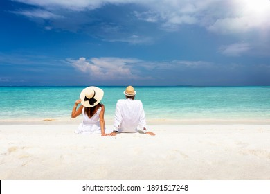 A romantic couple in white summer clothes sits hugging on a tropical beach in the Maldives and enjoys their vacation time