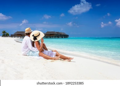 A romantic couple in white summer clothes sits hugging in the fine sand of a tropical beach in the Maldives