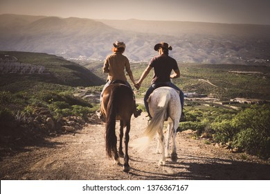 Romantic couple wide horses together holding hands with love and romance in outdoor leisure lifestyle alternative activity - viewed from back young people with aninmals