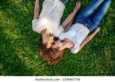 Romantic couple of young people lying on grass in park. Happy young couple in love in white shirts lying on green grass together. Top view.