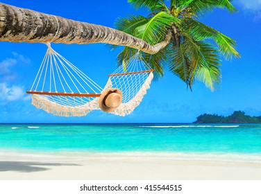 Romantic cozy hammock with straw hat in the shadow of coconut palm tree at tropical paradise ocean beach in bright sunny summer day - vacation background