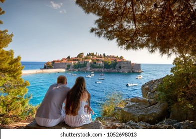 Romantic date. Couple enjoys the view of the island and the bay with boats and yachts from a hidden place on mountain.of Sveti Stefan.  Montenegro