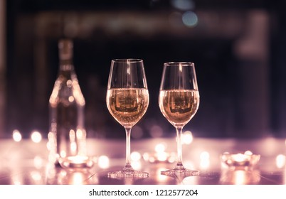 Romantic date night setting. Pair of wine glasses surrounded by candle lights.