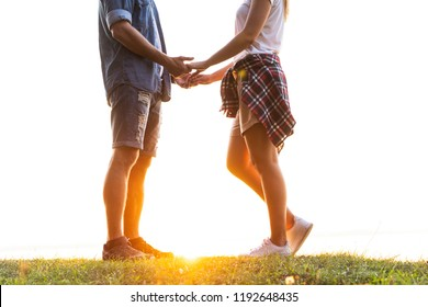 Romantic date outdoors. Young couple in love walking in the autumn park holding hands looking in the sunset