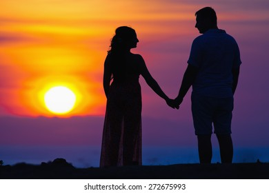 Romantic date of silhouette of couple at beautiful sunset background, they holding by hands