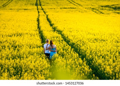 Romantic date in the spring nature. Yellow colza field standing together in beautiful yellow nature