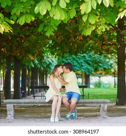 Romantic dating couple of tourist in Paris in the Tuileries garden, sitting on the bench and kissing on a late summer or autumn day