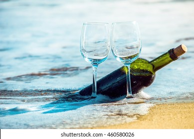 Romantic day with glasses of red wine sitting on the beach of tropical island at the summer sunny day. Waves and sea on the background. Wedding concept