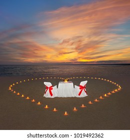 Romantic dinner with candles heart, luxury decorated table and wine at ocean tropical sandy beach during marvellous sunset. Proposal, wedding or honeymoon background concept.