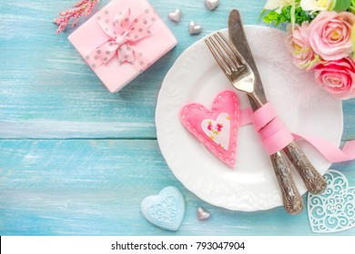 Romantic dinner concept. Table place setting with a white plate, vintage silverware tied with a pink ribbon and many different heart shape decorations, a gift and flowers With copy space