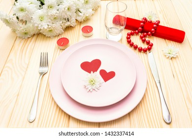 Romantic dinner concept. Valentines day, 8th march or wedding. Table setting, love hearts, gift and flowers. On wooden background.