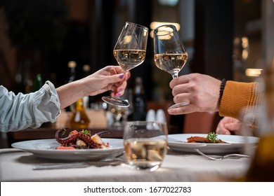 Romantic dinner. Couple cheers with white wine