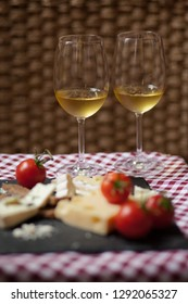 Romantic dinner for a couple on Saint Valentine's day: two glasses of cold white wine and gourmet french cheese plate with bread and fresh tomatoes. Nicely served on a red and white napkin