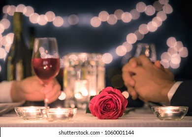 Romantic dinner date night. Focus on red rose.