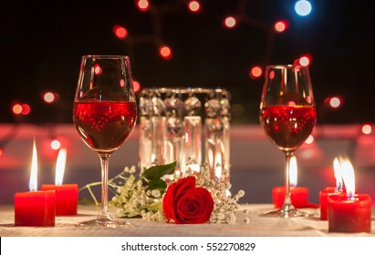 Romantic dinner. Focus on red rose.