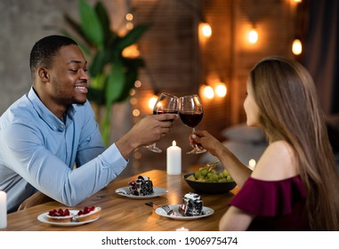 Romantic Dinner At Home. Loving Interracial Couple Dining In Elegant Domestic Atmosphere, Drinking Red Wine, Clinking Glasses And Eating Desserts, Celebrating Valentine's Day Or Anniversary Together