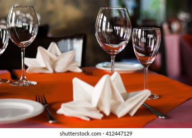 Romantic dinner interior, hotel service concept. Served table in a banquet hall. White plate knife fork and wine glasses on red napkin. Soft focus, shallow depth of field
