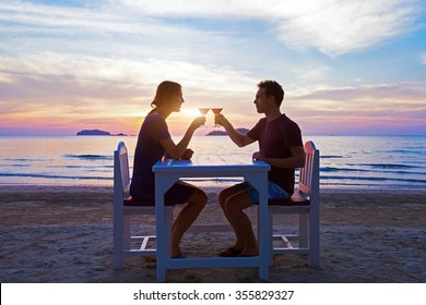 romantic dinner on the beach in luxury restaurant, couple on honeymoon drinking tropical cocktails at sunset