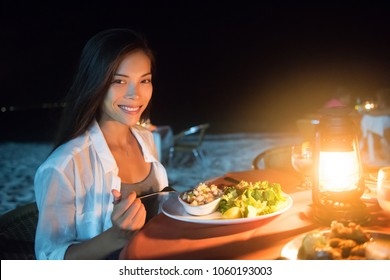 Romantic dinner on the beach at night at resort restaurant, Caribbean vacation luxury travel, Woman eating salad at table on sand near ocean with candlelight, honeymoon celebration.