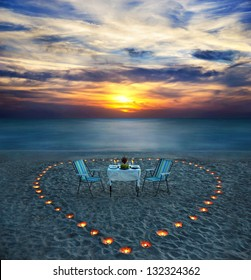 romantic dinner on sea beach with candle heart on the sand