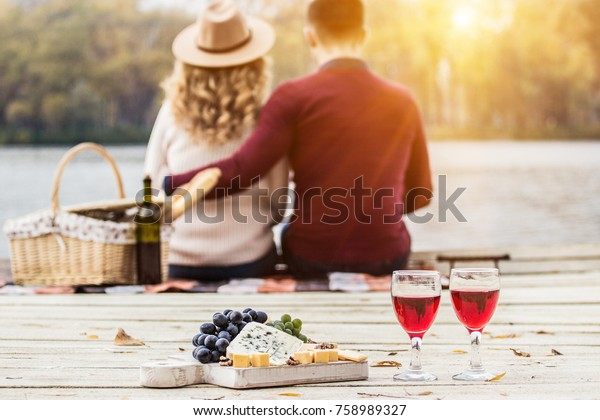 Romantic dinner outdoors. Glasses with red wine, grapes and cheese on wooden board. Young couple having romantic dinner outdoors. Back view man hugging her beautiful girlfriend. Couple in love.