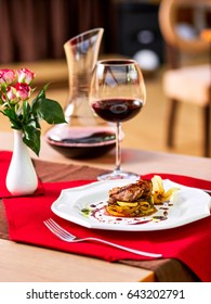 Romantic dinner in a restaurant, grilled meat with zucchini cheese and eggplant with red wine and small bouquet of nice flowers