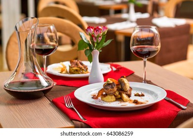 Romantic dinner in a restaurant. Grilled mushrooms and potato with wine