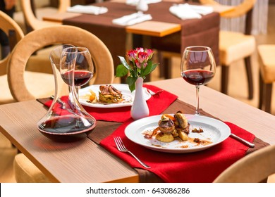 Romantic dinner in a restaurant. Grilled mushrooms and potato, fried meat and vegetables with wine.