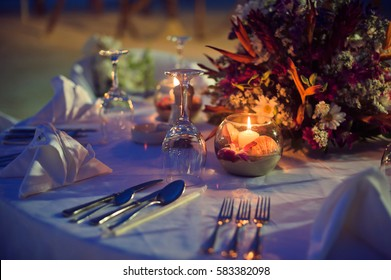 Romantic dinner setting on the beach at sunset. Wedding in the tropics concept
