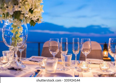 Romantic dinner setup, decoration with candle light, twilight. Selective focus.