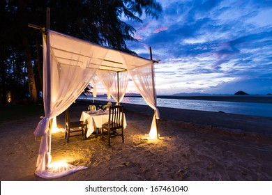 romantic dinner setup on the beach while twilight