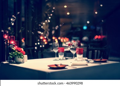 romantic dinner setup, red decoration with candle light in a restaurant. Selective focus. Vintage color.