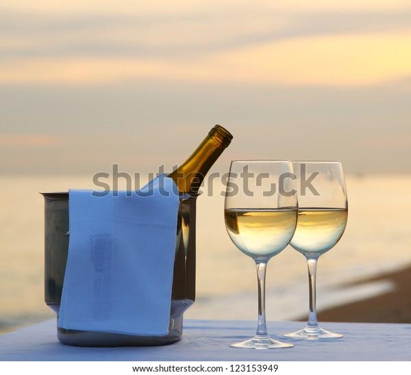 Een romantisch diner in de zomer op een strand bij zonsondergang met twee glazen witte wijn en een wijnkoeler