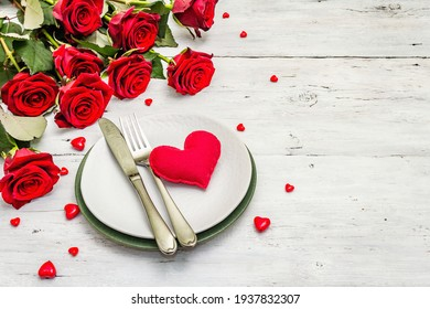Romantic dinner table. Love concept for Valentine's or mother's day, wedding cutlery. Bouquet of fresh burgundy roses, white vintage wooden boards background, place for text