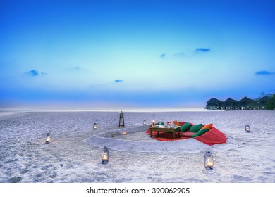 Romantic dinner table set for a wedding couple on the beach at twilight in the Maldives.