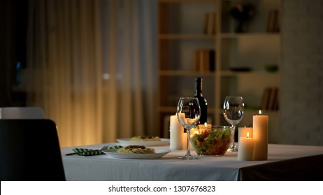 Romantic dinner table setting, wine glasses and fresh salad in bowl, home date