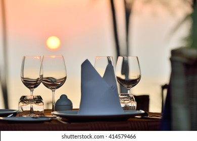 Romantic dinner table setup at a beach side restaurant on sunset.