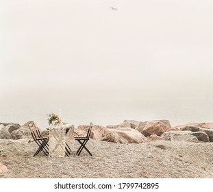 A romantic dinner for two is set up on a pebbled beach. The table is decorated with flowers, hand woven linens, and elegant chinaware. The water in the background remains a murky grey as the clouds ov