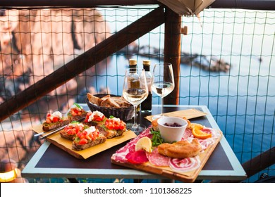 Romantic dinner for two at sunset. White wine and Tasty italian snack: fresh bruschettes  and meat on the board in outdoor cafe with amazing view in Manarola, Italy