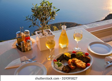 Romantic dinner for two at sunset.Greece, Santorini, restaurant on the beach, above the volcano. The view from the top.