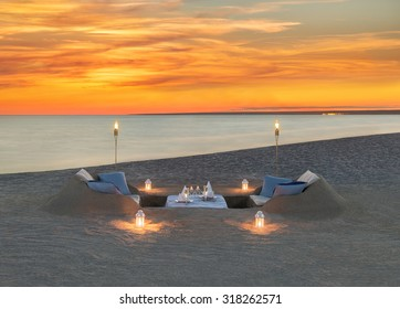 Romantic dinner with wine, candles, torches at sea beach during wonderful sunset. Honeymoon, proposal or wedding background concept.