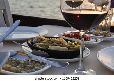 Romantic dinner. Wine at sunset. For Valentine's Day. For a marriage proposal. Octopus, shrimp, calamari, grilled fish, red wine, wonderful restaurant on the seaside.