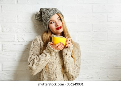 Romantic Dreaming Winter Hipster Girl in Knitted Sweater and Beanie Hat with a Mug in Hands at White Brick Wall Background. Warming Up Concept.