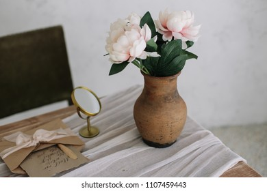 Romantic dressing table with a bouquet of peonies in a vase and a mirror. Boudoir. Bedroom interior in the vintage style