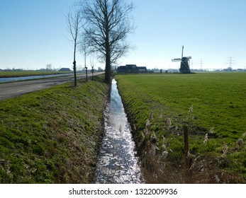 romantic dutch landscape with windmill  tree and river