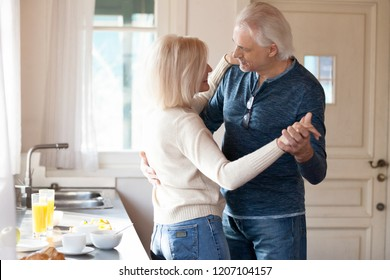 Romantic elderly couple look at each other waltzing in kitchen cooking food, happy aged husband and wife dance preparing breakfast at home, smiling senior man and woman sway enjoy time together