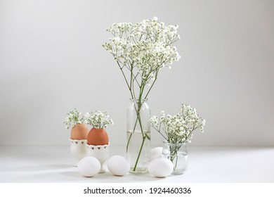 Romantic elegant bouquets with white flowers gipsophyla and eggs on light background. Copy space. Easter concept.