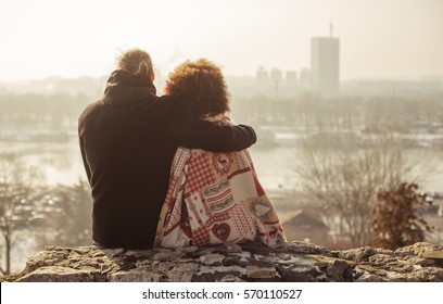 Romantic embracing loving couple enjoying the sunset in front of the city panorama. Falling in love